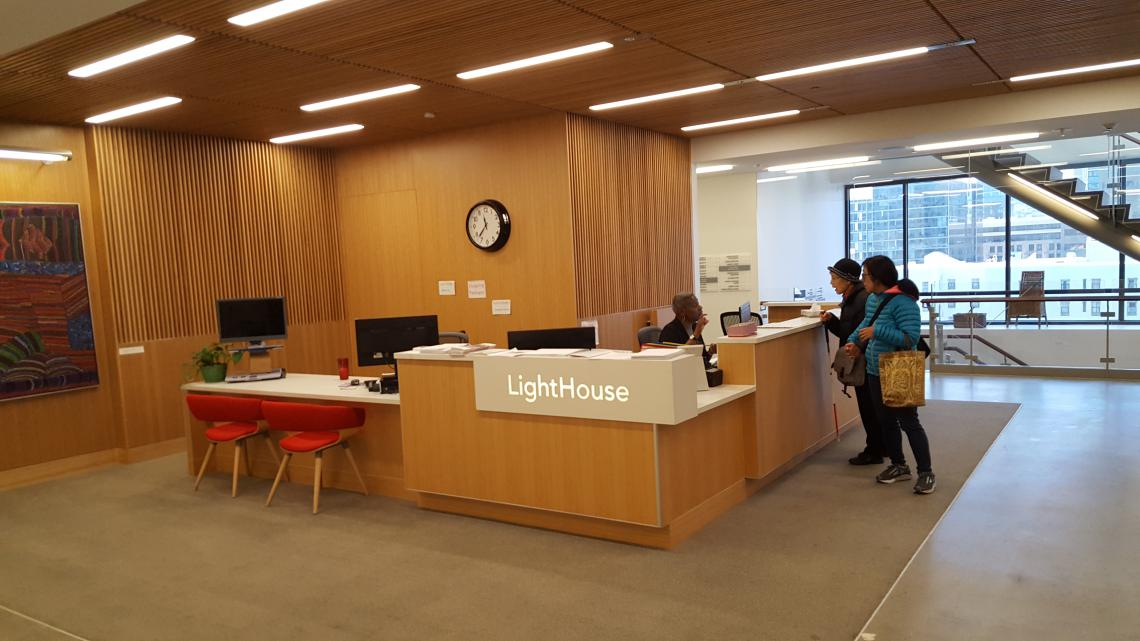 2 people speaking to the receptionist at the front desk in the main lobby of the Lighthouse for the Blind in San Francisco